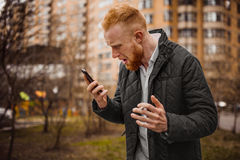 Angry man screaming on phone. Angry ginger man screaming on phone outdoor Stock Photography