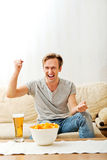 Angry man screaming while watching sports on tv Stock Photo