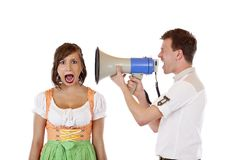 Angry man screams into ear of woman with megaphone Stock Photo