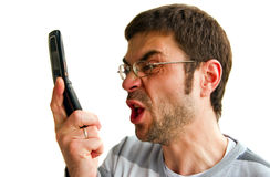 Angry Man Shouting. Portrait of a displeased furious man, he is talking by phone and screaming, isolated on white background Royalty Free Stock Images