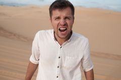 Angry man shouting accusing someone standing in desert Royalty Free Stock Photo