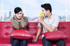 Angry man shouting against his girlfriend. Angry men shouting against his girlfriend with the help of a megaphone stock image
