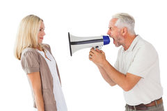 Angry man shouting at girlfriend through megaphone Royalty Free Stock Photography