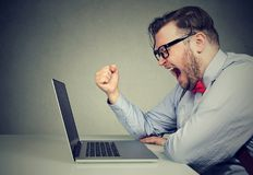 Angry man shouting at laptop. Side view of chubby young man in formal screaming in frustration while working with laptop royalty free stock image
