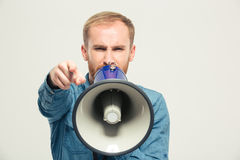 Angry man shouting in megaphone. Portrait of a young angry man shouting in megaphone and pointing finger at camera  on a white background Stock Photos