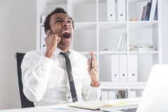 Angry man shouting on phone. Furious african american businessman sitting at office desk with laptop shouting at interlocutor over the phone on bookshelf Stock Photography