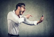 Angry man shouting at phone in hands. Side view of bearded man in glasses holding smartphone and yelling at it being rude Royalty Free Stock Photos