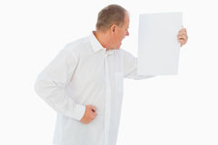 Angry man shouting at piece of paper Royalty Free Stock Image