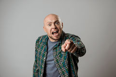 Angry man shouting, pointing finger at camera over beige background. Stock Image