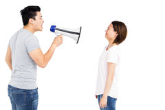 Angry man shouting at young woman on megaphone Stock Photo