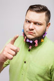 Angry man show finger. Portrait of a young man with colorful hair clips on his beard showing finger gesturing on white background Royalty Free Stock Photography