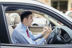 Angry man showing middle finger in car Stock Photos
