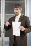 Angry man shows blanc sheet of paper. Angry man in business suit shows blanc sheet of paper Stock Photo