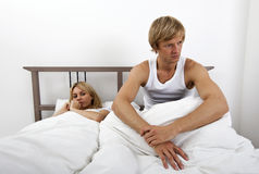 Angry man sitting on bed with woman in house Stock Photos