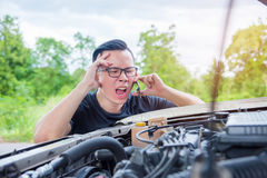 Angry man sitting beside a broken car calling for assistance Stock Image