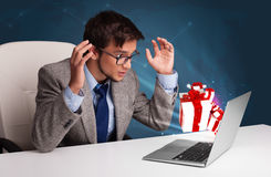 Angry man sitting at desk and typing on laptop with present boxe Stock Photos