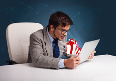 Angry man sitting at desk and typing on laptop with present boxe Royalty Free Stock Photography