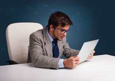 Angry man sitting at desk and typing on laptop Royalty Free Stock Images