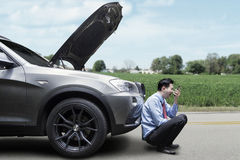 Angry Man Sitting near The Broken Car Royalty Free Stock Photos