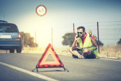 Angry man sitting on the road, talking by phone after a car breakdown Stock Images