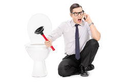 Angry man sitting by a toilet and talking on phone Stock Photos