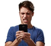 Angry man with smartphone. Angry young man with smartphone over white background stock photo