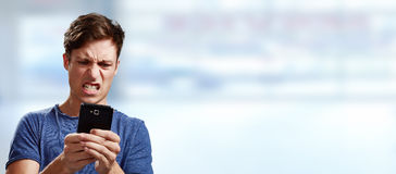 Angry man with smartphone. Angry young man with smartphone over blue background stock photos
