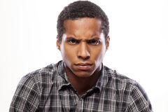 Angry man. Somber dark-skinned young man poses with angry expression royalty free stock images