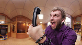 Angry man speaks on the phone Royalty Free Stock Photography