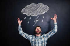 Angry man standing and shouting over blackboard with drawn raincloud Stock Images