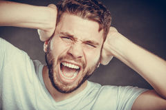 Angry man suffering from headache migraine pain. Royalty Free Stock Images