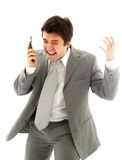 Angry Man in Suit with Mobile Phone. Angry business man with cellular phone over white Royalty Free Stock Photos