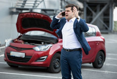 Angry man talking by phone because of broke down car Stock Image