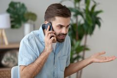 Angry man talking on smartphone solving work problem. Angry man talk on smartphone arguing or solving problem, irritated male have cell phone conversation manage stock photo