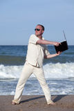 Angry man throwing his laptop at the beach. Sunburnt businessman at the beach throwing his laptop. Concept of protesting against work on vacation Royalty Free Stock Image