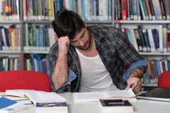 Angry Man With Too Much Paperwork to Do. Stressed Student in High School Sitting at the Library Desk Stock Photos