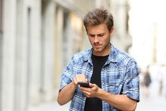 Angry man touching smart phone screen. Angry man touching crashed smart phone screen in the street stock photos
