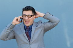 Angry man using a cell phone on a blue background.  Stock Photos