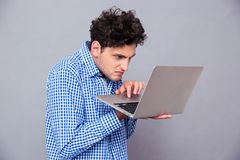 Angry man using laptop Royalty Free Stock Image