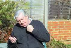Angry man using a mobile phone. An elderly man sitting outside using a mobile phone. the man is very angry at something or someone talking to him on the phone Stock Images