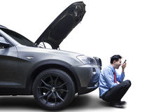 Angry Man Using Phone by Broken Car Stock Image
