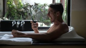 Angry Man using Smartphone while lying in Bathtub in Bathroom. Man got a bad message and shows anger. Danger Violence. Angry Man using Smartphone while lying in stock video footage