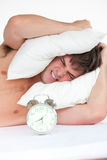 Angry man waking up by his alarm clock Royalty Free Stock Image