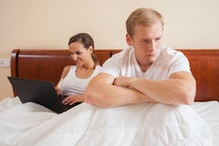 Angry man because of woman's addiction Stock Photography