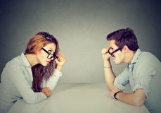 Angry man and woman sitting at table looking at each other with hatred and disgust. Angry men and women sitting at table looking at each other with hatred royalty free stock photos