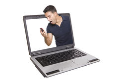 Angry man yelling to his cellphone. An angry man yelling to his cellphone inside of a laptop Royalty Free Stock Images