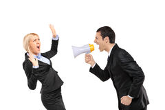 Angry man yelling via megaphone to a scared woma Stock Photos