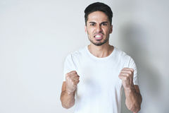 Angry man. Young man is fighting. Serious man is angry and wants second try, standing in a white loose t-shirt with hands in fists against grey background Stock Image