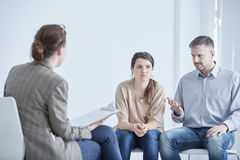 Angry married couple with psychologist. Angry married couple talking with psychologist during therapy Royalty Free Stock Photos