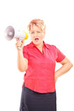 Angry mature lady speaking on a megaphone Stock Image
